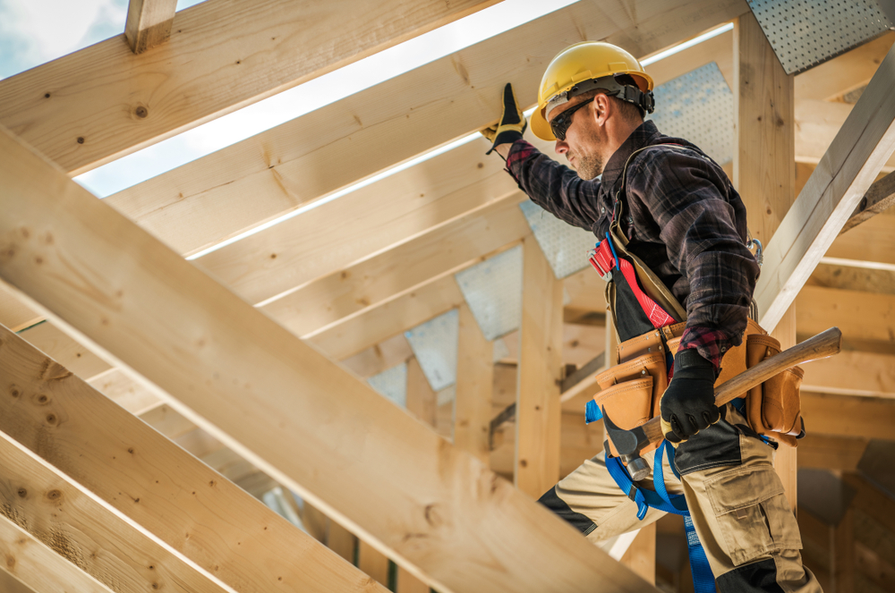 An image of a builder working on the frame of a new home.