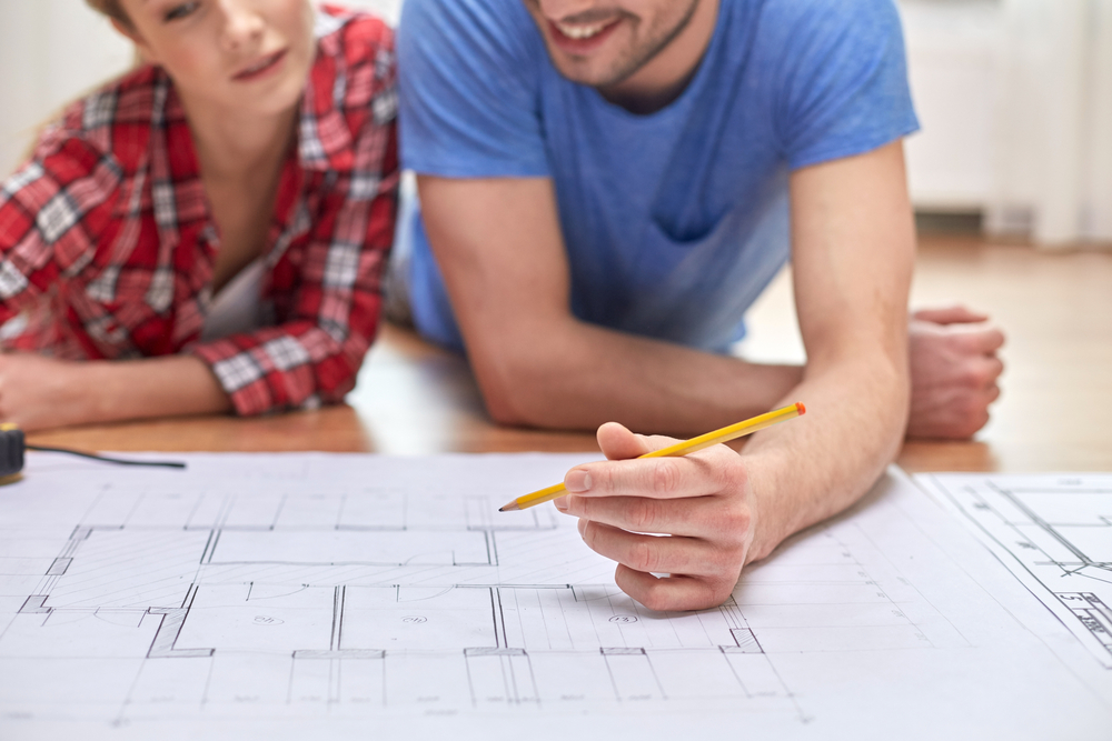 An image of a young couple looking at building plans.