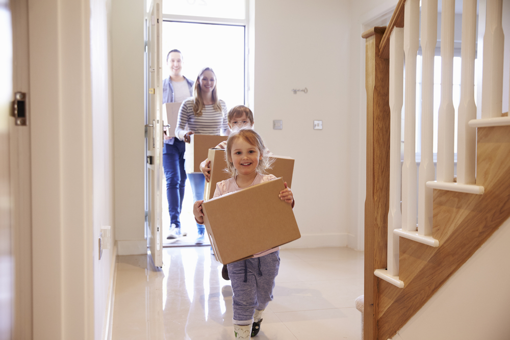 A young family walking into their new home with boxes.